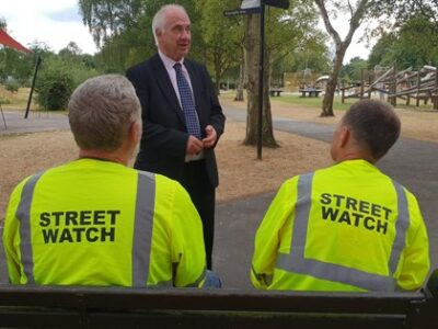 PCC chats with 2 StreetWatch volunteers wearing high visibility jackets with StreetWatch logo